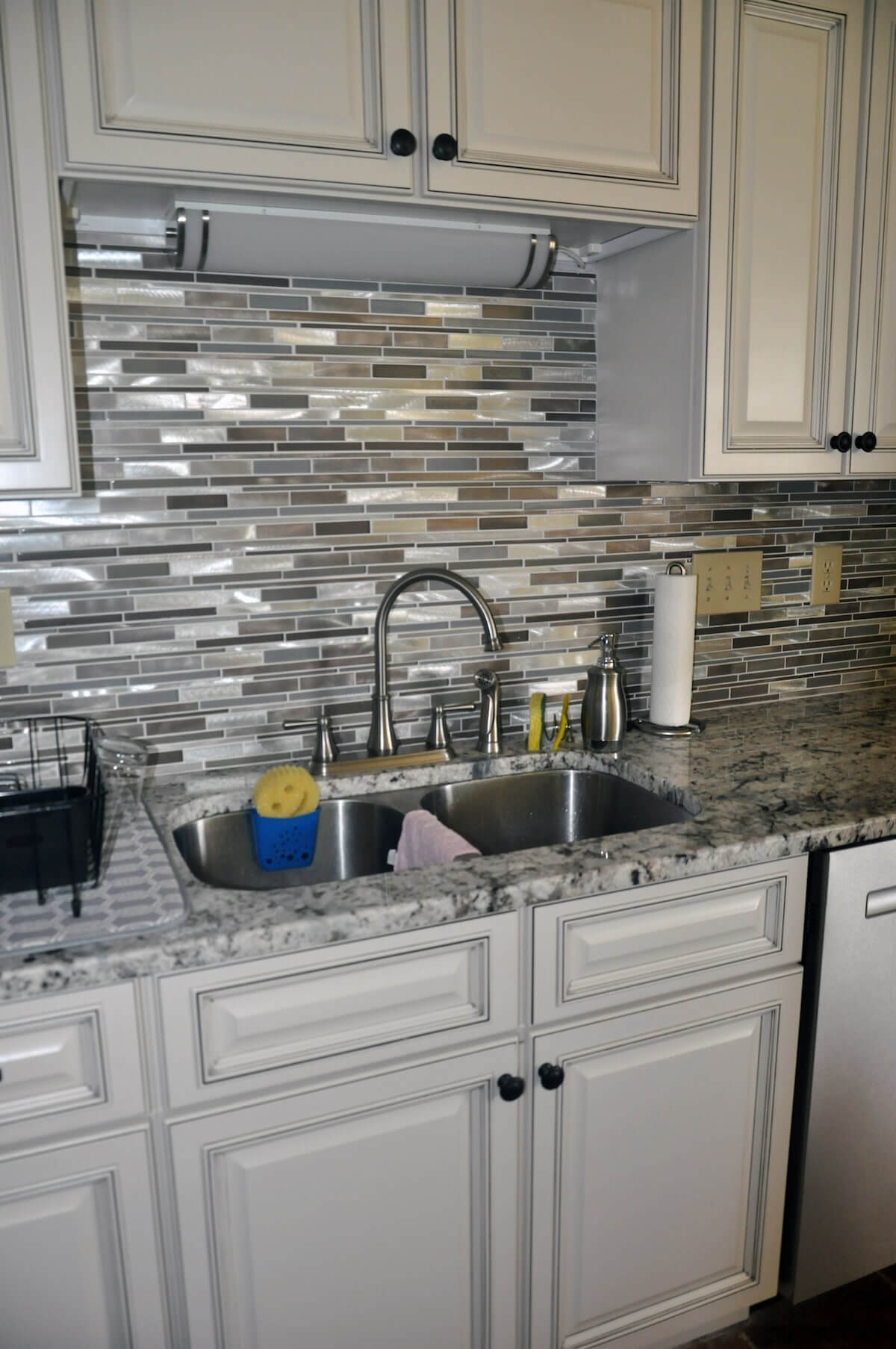 Silver tile backsplash with stainless steel sink