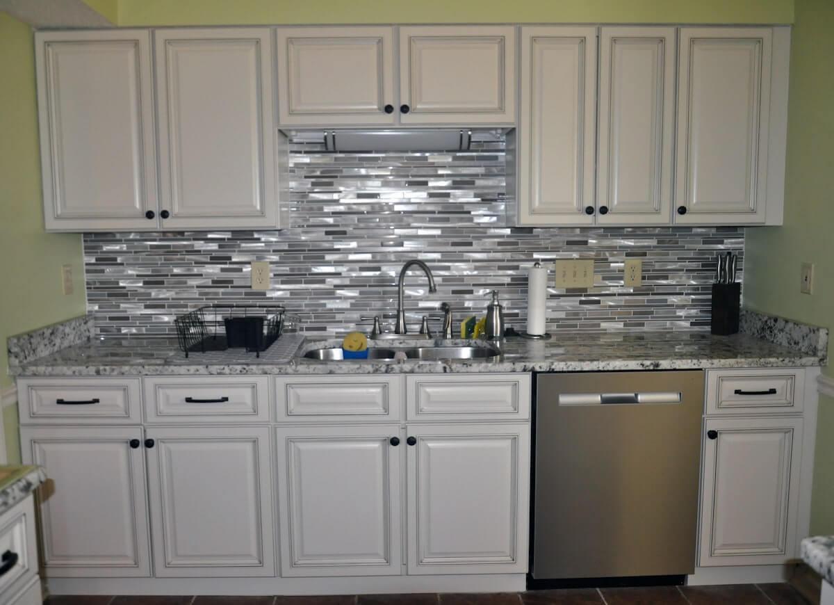 White cabinets with silver kitchen backsplash