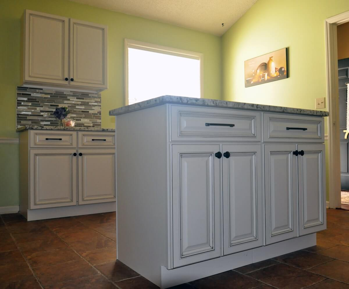 White cabinets with island and granite countertops